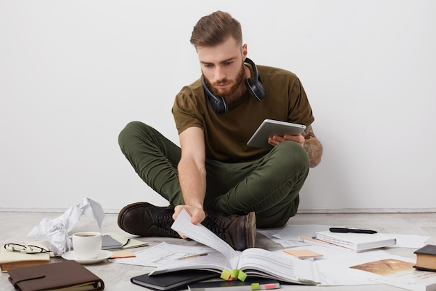 Preoccupied beared male college student with trendy hairdo looks attentively into book, holds modern tablet