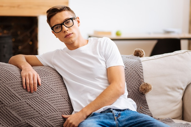 Preoccupied. handsome meditative fair-haired young man wearing glasses and looking in the distance and thinking while sitting on the sofa