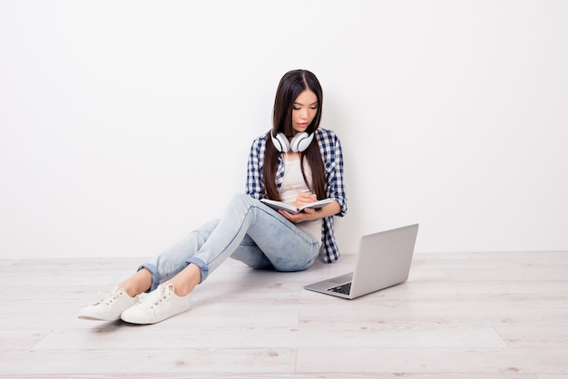 Озабоченная дама сидит на полу и пишет в блокноте с помощью компьютера