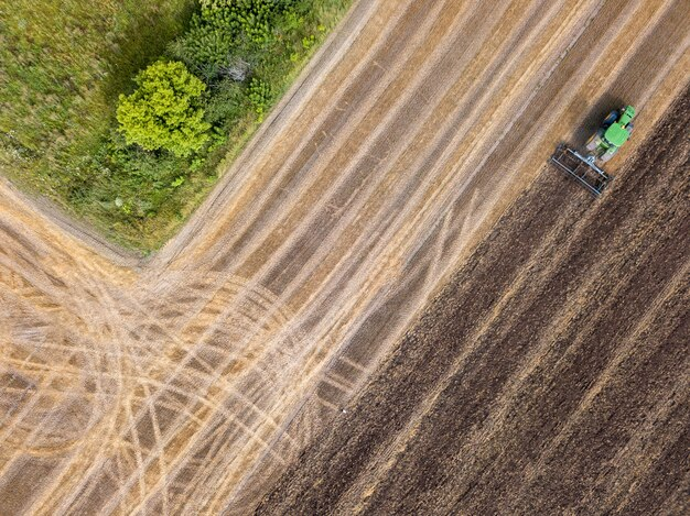 Preparation of agricultural areas for sowing works, cultivation of the soil by a tractor after harvesting. aerial view from drone.