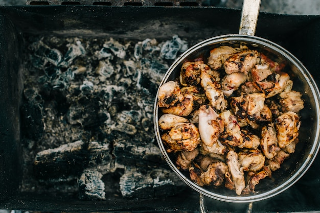 Preparation on bbq.  dish with roasted meat on abstract background.  hot tasty smokey barbecue meal at coals and burnt firewood.  cooking on fire outdoor.  nice smelling food.  fried chicken pieces