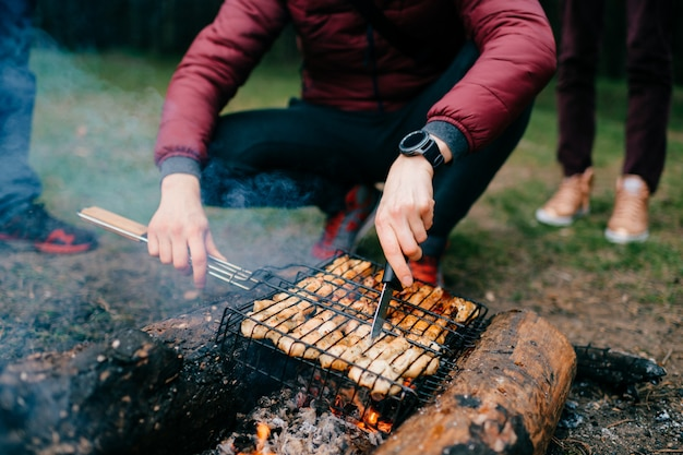 Preparation on bbq.  dish with roasted meat on blurred grass.  hot tasty smokey barbecue meal at coals and burnt firewood.  cooking on fire outdoor.  nice smelling food.  fried chicken pieces