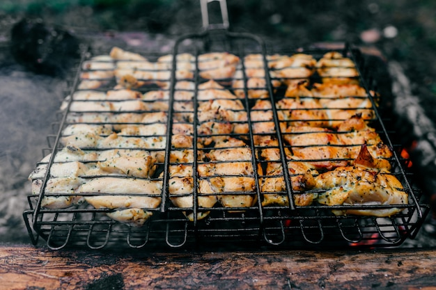 Preparation on bbq.  dish with roasted meat on blurred grass.  hot tasty smokey barbecue meal at coals and burnt firewood.  cooking on fire outdoor.