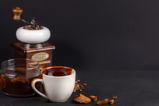 Preparation chaga mushrooms coffee. white-brown cup and glass jar of chaga drink, coffee grinder on black background.