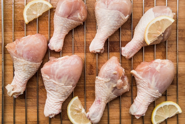 Preparation of chicken drumsticks on metal grill over wooden table with lemons