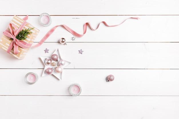 ピンクの装飾が施された白い木製のテーブルにクリスマスプレゼントを準備します。フラットレイ、上面図、コピースペース、バナー