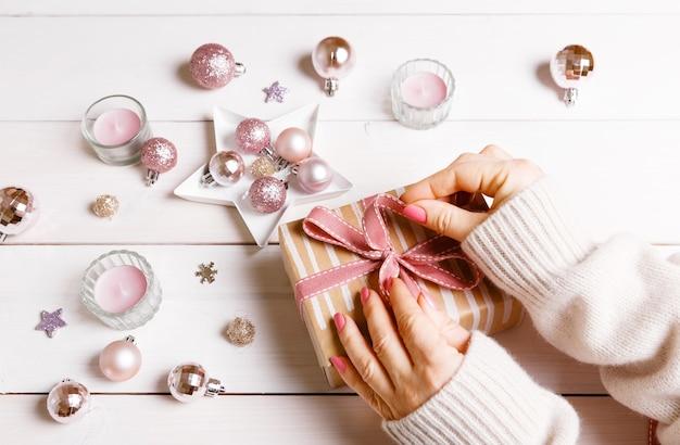 ピンクの装飾が施された白い木製のテーブルにクリスマスプレゼントを準備します。フラットレイ、上面図、コピースペース