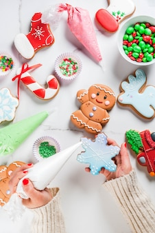 Preparation for christmas, the girl hands in the picture decorates homemade handmade traditional gingerbread with multicolored sugar icing, biscuits, white marble table. top view