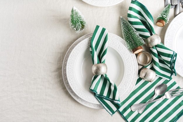 Preparation to christmas table setting with white plates, cutlery, napkin and christmas decor on linen tablecloth with copy space. winter, festive concept table serving for new year.