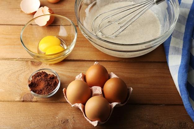 木製のガラスのボウルに卵と準備クリーム