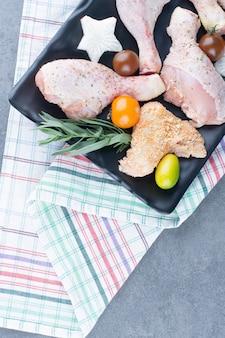 Preparazione per la cena con piatto di cosce di pollo crude.