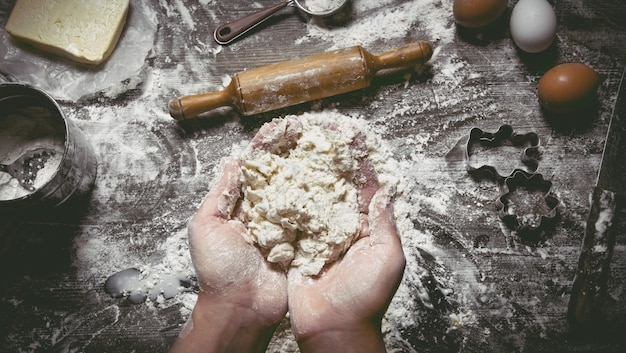 Preparation of dough. dough women's hands and tools. sieve, rolling pin, knife, whisk on wooden table. top view