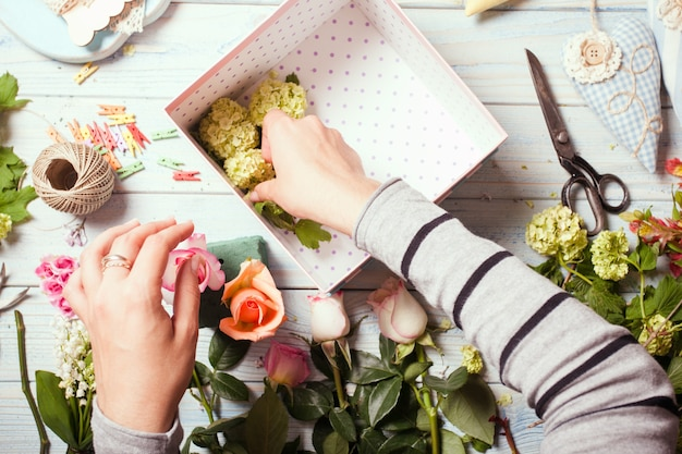 Preparation of flower box with macaroons, top view of florist workplace