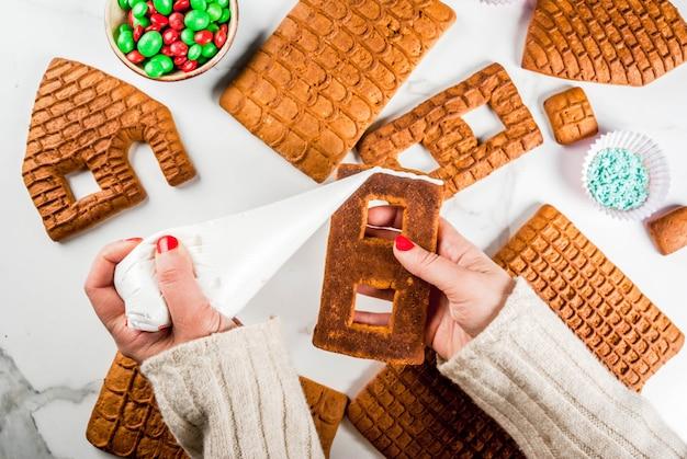 Подготовка к рождеству, новый год. приготовление и украшение традиционного пышного дома пришествия, женские руки в изображении, вид сверху, белый мрамор.