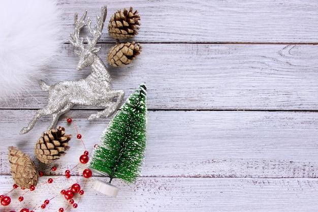 白い木製の背景にクリスマスシルバー鹿のおもちゃの木の円錐形と赤いビーズの準備。テキストのクリスマスコンセプトスペース