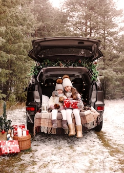 クリスマスの準備。 10代の子供たちは、車のトランクでクリスマスプレゼントを楽しんでいます。寒い冬、雪の降る天気。