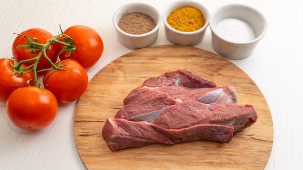 커팅 보드에 향신료와 토마토와 쇠고기 고기의 원시 resh 조각 요리 준비