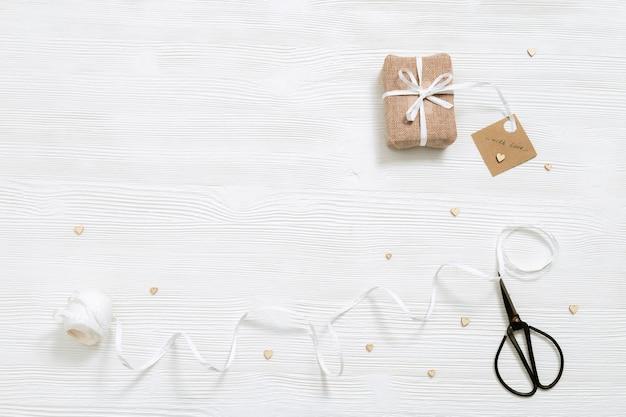 Подготовка к празднику самодельная подарочная коробка для подарков, завернутая в крафт-ткань на белом дереве