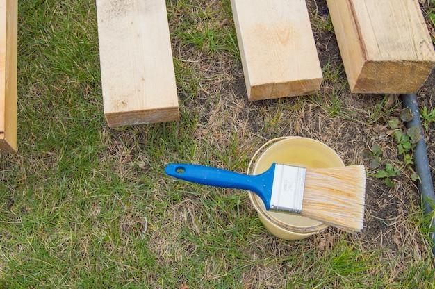 잔디에 누워 있는 새 나무 판자를 칠하기 위한 준비, 양동이가 있는 페인트 브러시.