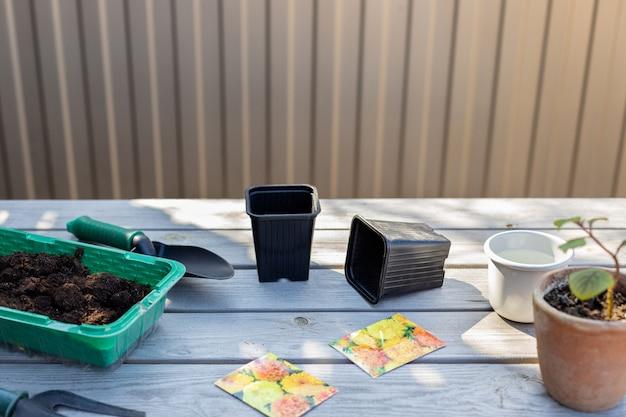 花の種園芸工具、苗鉢、裏庭の木製のテーブルに土を植えるための準備