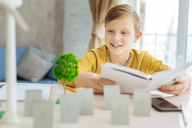 Подготовка к тесту. улыбающийся мальчик подросткового возраста читает книгу, пересматривает абзац об альтернативной энергии и смотрит на миниатюры деревьев, солнечных батарей и ветряных турбин.