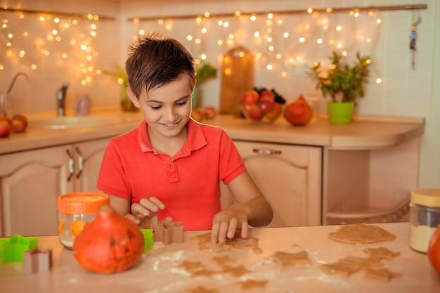 ホリデーハロウィーンの準備。幸せな陽気な少年が台所でクッキーを調理