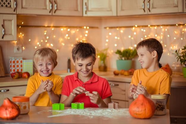 ホリデーハロウィーンの準備。 3人の陽気な子供がキッチンでクッキーを作る