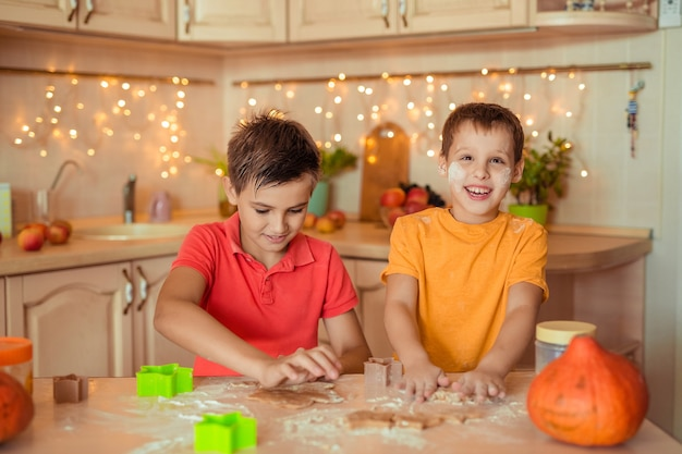 ホリデーハロウィーンの準備。 2人の陽気な子供がキッチンでクッキーを作る