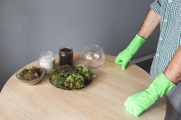 실내 식물 이식 준비. 테이블에 근접 촬영은 이끼와 다육 식물, 흙이 든 용기, 다육 식물을위한 유리 식물상, 녹색 장갑을 든 손입니다.