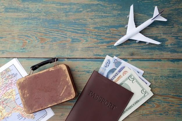 旅行の概念の準備。お金、パスポート、飛行機、スーツケース、ヴィンテージの木製の背景の地図。