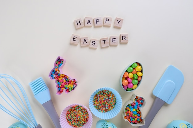 Preparation of gingerbread cookies. easter cookies cutters, tools necessary to make gingerbread pastry, colored sprinkles. easter concept.with letters text