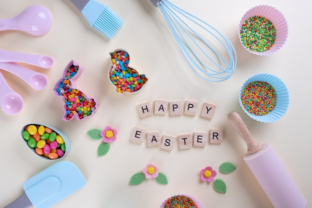 Preparation of gingerbread cookies. easter cookies cutters, tools necessary to make gingerbread pastry, colored sprinkles. easter concept. with letters text