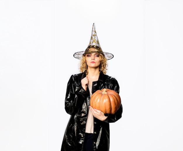 Подготовка к праздникам хэллоуина женщина ведьма с тыквой счастливых праздников хэллоуина эмоциональная женщина в