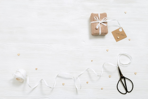 Preparation for holiday homemade gift present box wrapped in kraft cloth on white wood