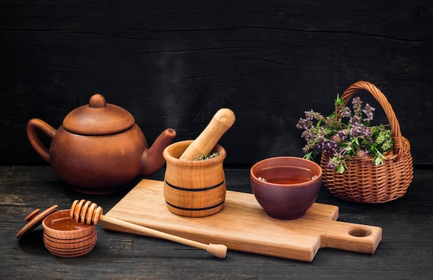 Preparation of hot medicinal tea, from thyme and honey on a black wooden background