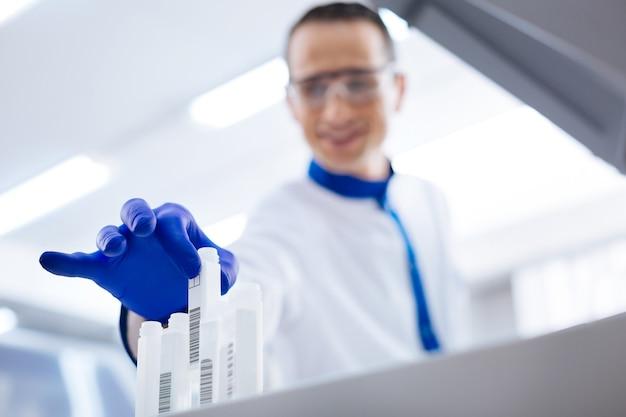 準備中。透明な容器を引き出してfbsの準備をしている青い手袋をはめて笑顔の真面目な男性研究所