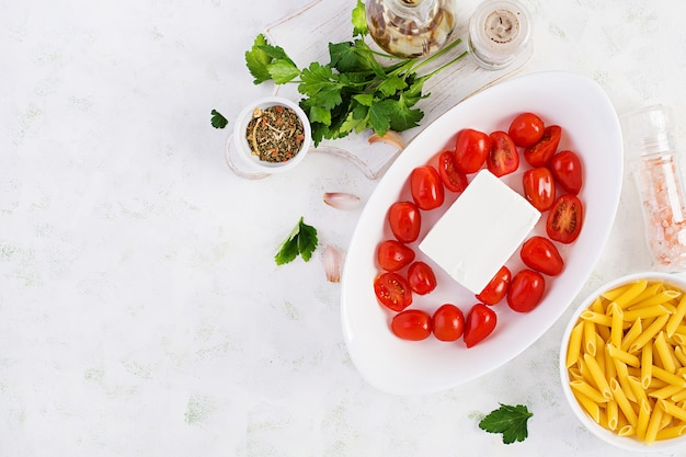 Preparation of ingredients for fetapasta. trending feta bake pasta recipe made of cherry tomatoes, feta cheese, garlic and herbs.  top view, above, copy space.