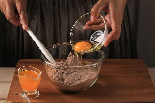 Приготовление смешивание растопленного шоколада и какао-порошка в миске для приготовления теста для вкусного пирога брауни на деревенском деревянном столе с венчиком, добавление яичного желтка в миску