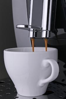 전문 커피 머신에서 아침 블랙 아로마 아메리카노 커피 원두를 준비합니다. 핫 웨이크