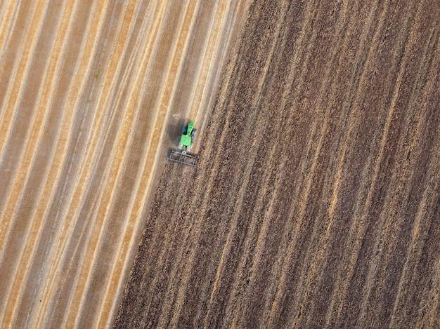 播種作業のための農業地域の準備、収穫後のトラクターによる土壌の耕作。飛行ドローンからの空中上面図