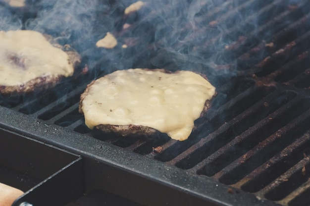 가족 바베큐 날 바베큐 파티에서 치즈 버거 준비. 그릴에 올려진 뜨거운 패티에 치즈가 녹는다.