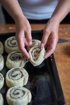 Приготовление булочек с корицей. женщина ставит булочки с булочками на противень.