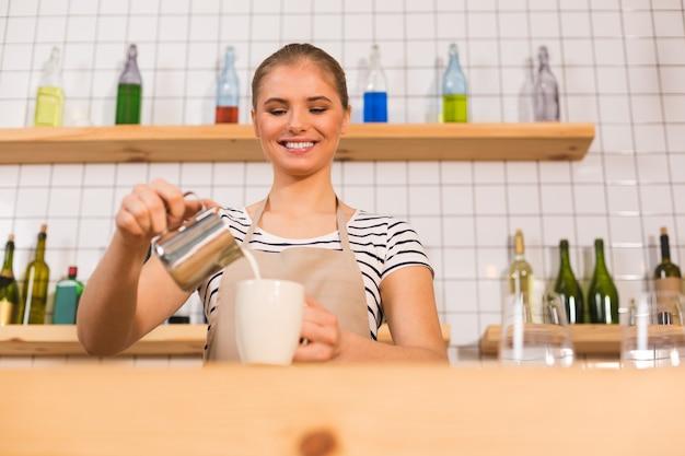 コーヒーの準備。エプロンを着て、コーヒーを準備しながらカップにミルクを注ぐ幸せな素敵な熟練した女性