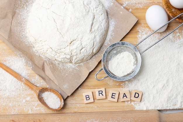 朝食用の家庭用パンケーキの生地の準備。テーブルの上の材料小麦粉、卵。碑文パン