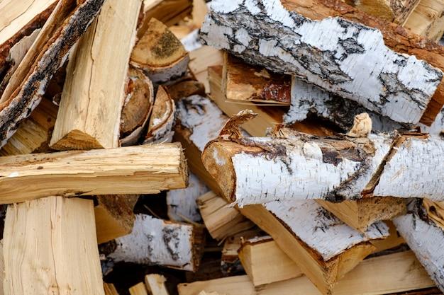 冬の薪の準備。薪の背景、森の薪のスタック。薪の山。
