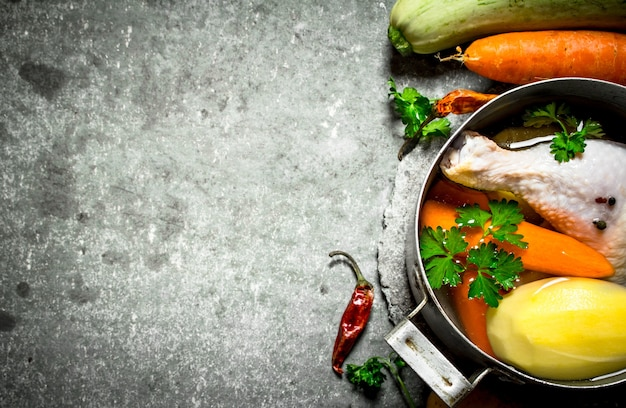 Приготовление ароматного куриного супа из свежих овощей. на каменном столе.