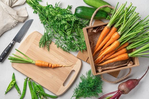 Приготовление свежих овощей. морковь, кабачки, горох, свекла и зелень на сером фоне.