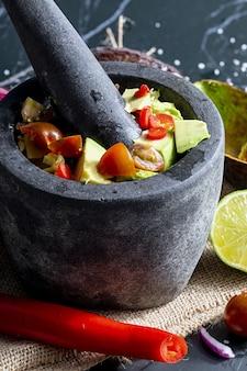 Приготовление гуакамоле в традиционной каменной ступке со всеми его ингредиентами нарезанный авокадо, лук, лайм, помидоры и перец чили. традиционный гуакамоле. домашний вид