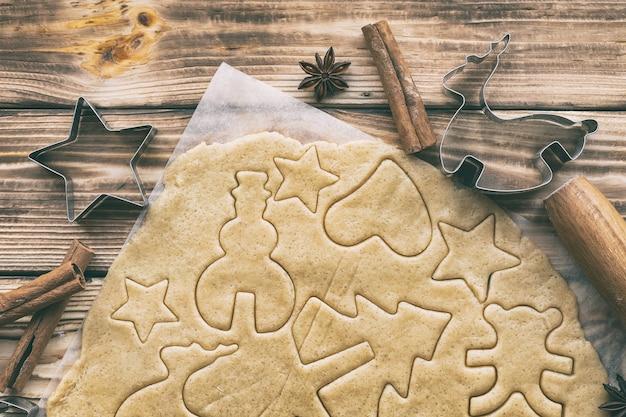 Приготовление домашнего рождественского или новогоднего печенья в формочках на пергаментной крафт-бумаге на деревянных досках