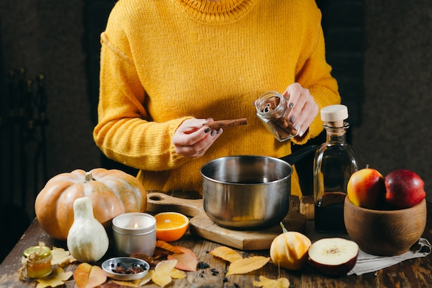 グリューワインの準備ホットグリューワインにシナモンの棒を追加する黄色いセーターの女性の手